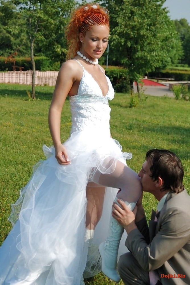 Жених целует свою невесту между ног на свадьбе