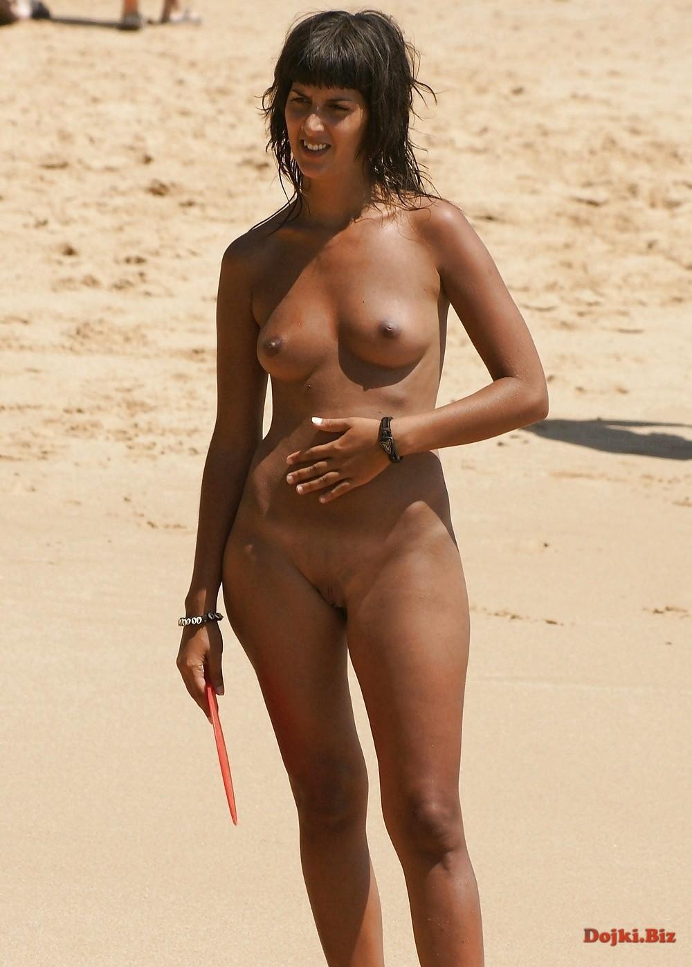 Стоит на пляже загорает