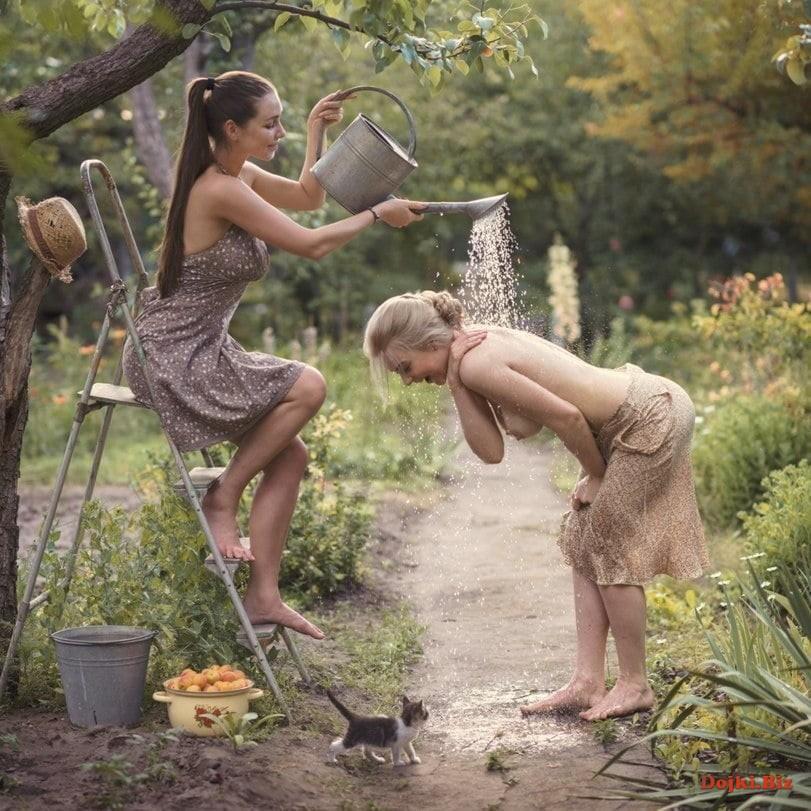 Девушки в деревне прохлаждаются поливая на себя из садовой лейки