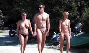 Две голые девушки и парень идут на нудистский пляж фото