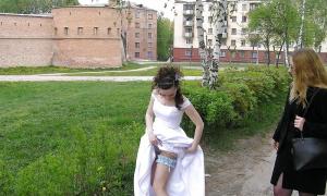 Невеста поправляет на ноге свадебную подвьязку