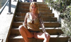 Аппетитная девочка сидит на ступеньках раздвинув ноги