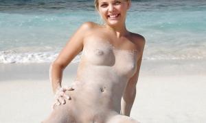 Испачканная песком голая девушка на пляже