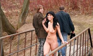 Красивая без одежды на мостике перед мужиками