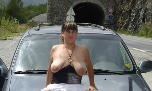 На капоте машины сидит обнажила аппетитную щелку и сиськи