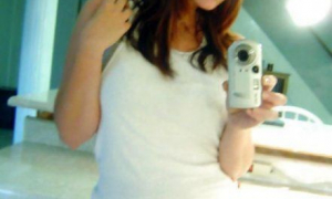 Милашка в маечке перед зеркалом фото