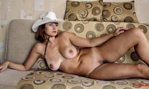 Голая в шляпе ковбоя на диване лежит фото