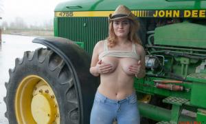 Ковбойша на ферме возле трактора обнажила грудь