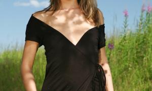 На природе гуляет девушка в черном платье без трусов фото