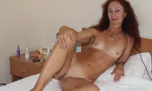 Обнаженная зрелка с плоской грудью позирует перед сексом на кровати фото
