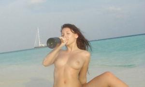 Топлесс в трусиках на пляже с бутылкой вина фото